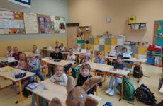 dzieci pozujące do zdjęcia w klasie